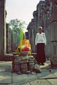 old lady at Buddha statue at Bayon Angkor Park