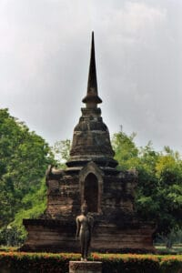 Buddha statue in front of ancient stupa in Sukhothai
