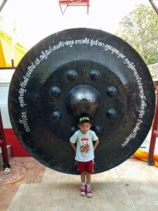 boy in front of huge gong in Wat Doi Kham