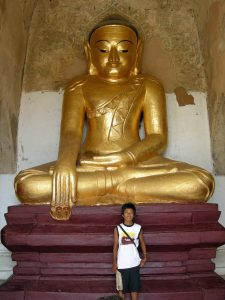 guide proudly posing in front of Buddha statue